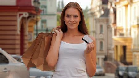 oferta : Young girl with shopping bags looking at camera and smiling. Woman holding credit card. Shopping and tourism concept - beautiful girls with shopping bags and credit card in city