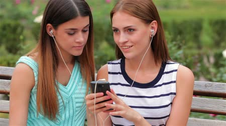 outside : Two attractive girls listening to music on the smartphone. Young woman enjoying the music sitting on the bench in the city. Rest and relax after shopping. Stock Footage