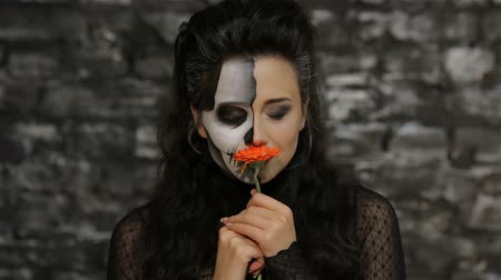 kostüm : A woman smelling a flower. Beautiful woman with make-up skeleton posing on black background of a brick wall. Halloween concepts and costumes.