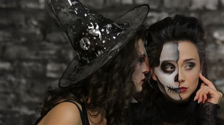 wampir : Enchantress whispers skeleton. Women in the image of the skeleton and the sorceress posing on black background of a brick wall. Halloween concepts and costumes. Wideo