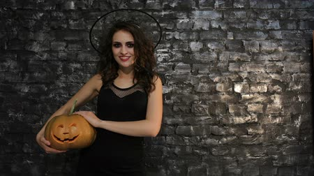 indicação : Woman-sorceress shows the side copyspace. Women in the image of the sorceress posing on black background of a brick wall. Halloween concepts and costumes.