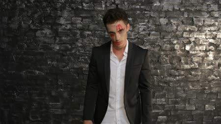 wampir : Hungry vampire pounced. Man in the image of the vampire posing on black background of a brick wall. Halloween concepts and costumes. Wideo