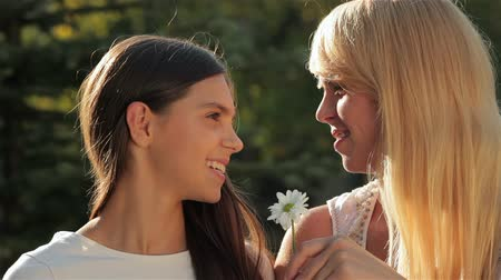 csókolózás : A mother and her teenage daughter sniffing camomile. Happy mother with her daughter in park outdoors. Teenage girl outdoor with her mom. Portrait of mother with teenager daughter.