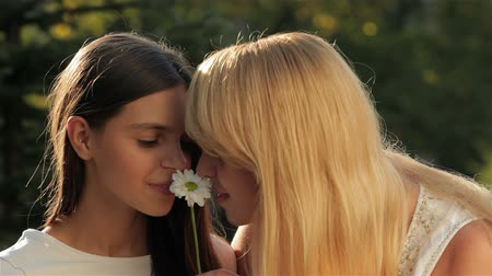 csókolózás : A mother and her teenage daughter sniffing chamomile and kiss. Happy mother with her daughter in park outdoors. Teenage girl outdoor with her mom. Portrait of mother with teenager daughter.