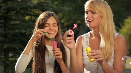 den matek : A mother and her teenage daughter blowing bubbles. Happy mother with her daughter in park outdoors. Teenage girl outdoor with her mom. Portrait of mother with teenager daughter. Dostupné videozáznamy