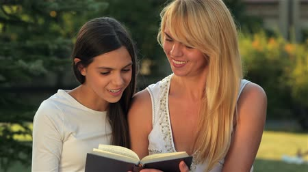 den matek : Mom and daughter reading a book on a bench park. Happy mother with her daughter in park outdoors. Teenage girl outdoor with her mom. Portrait of mother with teenager daughter. Dostupné videozáznamy
