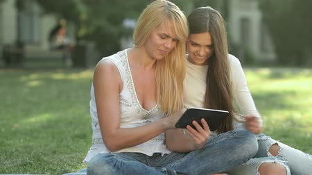 csókolózás : Daughter and mother sitting on the grass using a tablet. Happy mother with her daughter in park outdoors. Teenage girl outdoor with her mom. Portrait of mother with teenager daughter. Stock mozgókép