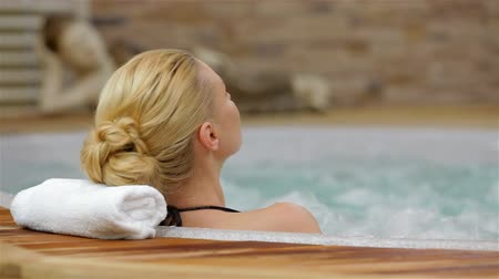 hidromassagem : Back view of a woman enjoying hot tub. Back view of a young woman enjoying hot tub in a spa center. Happy woman relaxing in hot tub. Woman in spa salon.