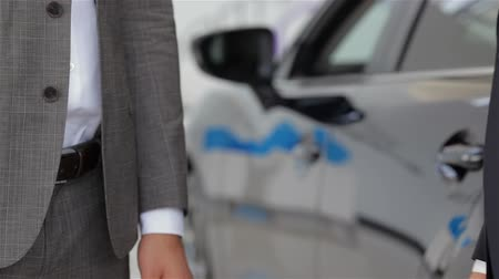 Good deal. Close-up shoot of the hands shaking in front of the car. Auto business, car sale, technology and people concept - happy male with car dealer in auto show or salon. Young man with a salesman in a motor show.