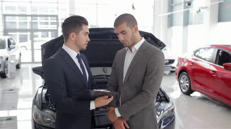 sala de exposição : Look at these tires! Young car salesman showing the advantages of the car to the customer. Auto business, car sale, technology and people concept - happy male with car dealer in auto show or salon. Young man with a salesman in a motor show.