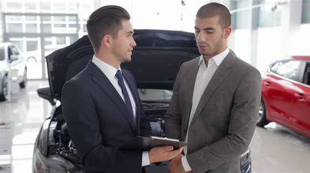 sprzedawca : Young man with a salesman in a motor show. Auto business, car sale, technology and people concept - happy male with car dealer in auto show or salon. Young man with a salesman in a motor show.