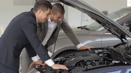 revendedor : Auto business, car sale, technology and people concept - happy male with car dealer in auto show or salon. Young man with a salesman in a motor show.