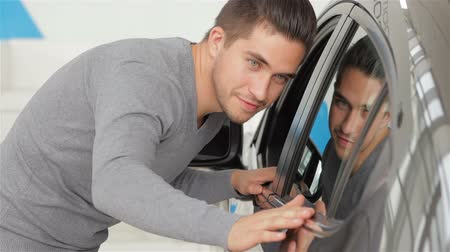 sala de exposição : A man inspects his new car color. Auto business, car sale, technology and people concept - happy male with car dealer in auto show or salon. Young man with a salesman in a motor show.