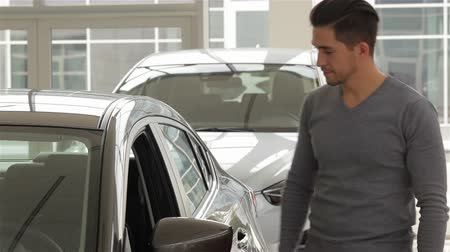 new car : A man inspects interior of the vehicle. Auto business, car sale, technology and people concept - happy male with car dealer in auto show or salon. Young man with a salesman in a motor show.