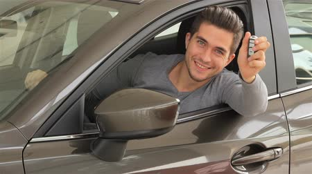new car : Happy man showing the key of his new car. Auto business, car sale, technology and people concept - happy male with car dealer in auto show or salon. Young man with a salesman in a motor show. Stock Footage