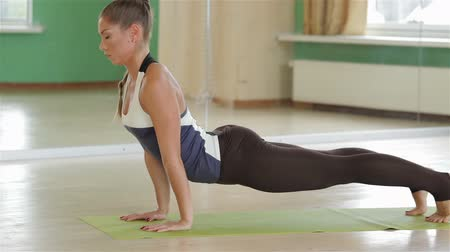 ćwiczenia : beauty practicing gymnastic yoga. Fitness, yoga, sport, training, gym and lifestyle concept - stretching young woman in the gym. Young girls do yoga indoors.