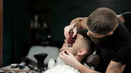 борода : Mens hairstyling and haircutting in a barber shop or hair salon. Grooming the beard. Barbershop. Man hairdresser doing haircut beard adult men in the mens hair salon. Hairdressers in the workplace. Barber.