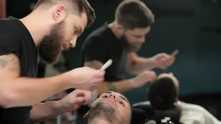 kadeřník : Mens hairstyling and haircutting in a barber shop or hair salon. Grooming the beard. Barbershop. Man hairdresser doing haircut beard adult men in the mens hair salon. Hairdressers in the workplace. Barber.