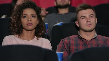 divadlo : Young couple at the cinema. Cinema, entertainment and people concept - happy friends watching movie in theater. Couple and other people eating popcorn and drinking soda while watching movie at the cinema. Dostupné videozáznamy