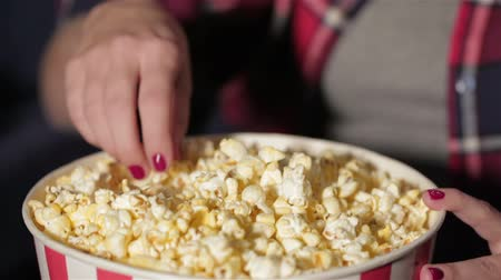 kino : Close up bucket of popcorn and a hand of the girl. She chews popcorn while watching a movie. Cinema, entertainment and people concept - happy friends watching movie in theater. Couple and other people eating popcorn and drinking soda while watching movie  Wideo