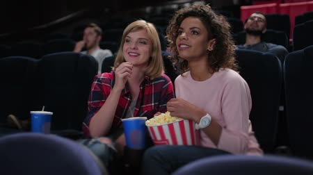 hossz : Young woman eating popcorn and watching movie together while sitting at the cinema. Cinema, entertainment and people concept - happy friends watching movie in theater. Couple and other people eating popcorn and drinking soda while watching movie at the ci
