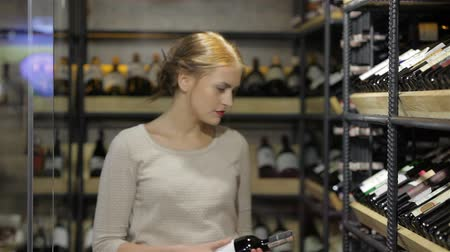 kırmızı şarap : Young female deciding which wine to buy at the supermarket. Sale, shopping, consumerism and people concept - happy young woman or male choosing and buying wine or beer in market or liquor store. Adult happy european shoppers choosing bottle of wine at liq