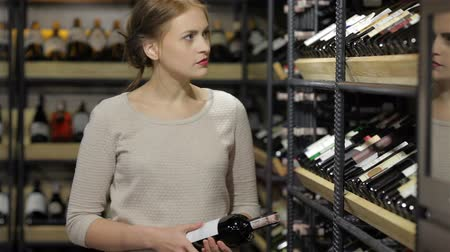 vinho : Young woman shopping in the supermarket, wine shelves. Sale, shopping, consumerism and people concept - happy young woman or male choosing and buying wine or beer in market or liquor store. Adult happy european shoppers choosing bottle of wine at liquor s