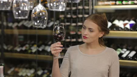 vinho : Beautiful young woman tasting red wine in a wine cellar. Sale, shopping, consumerism and people concept - happy young woman or male choosing and buying wine or beer in market or liquor store. Adult happy european shoppers choosing bottle of wine at liquor