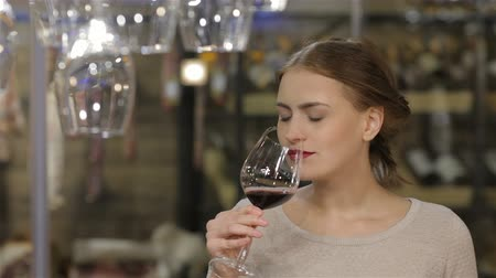 kırmızı şarap : Woman drinking wine. Beautiful young woman drinking wine and keeping eyes closed. Sale, shopping, consumerism and people concept - happy young woman or male choosing and buying wine or beer in market or liquor store. Adult happy european shoppers choosing