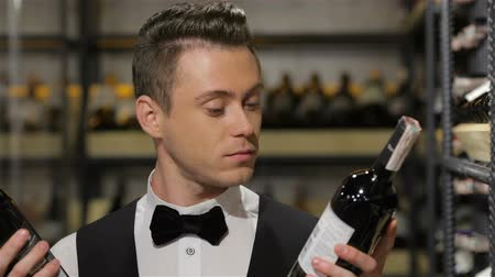 alışveriş : I know everything about wine. Confident male sommelier  smiling at camera while leaning wine, bottle shelf in the background. Sale, shopping, consumerism and people concept - confident and experienced sommelier. Best choice of wine. Stok Video