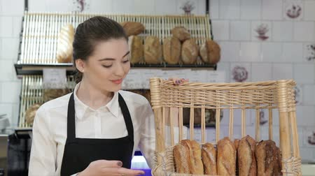 acıbadem kurabiyesi : The girl seller offers bread. Young smiling baker inside the coffee shop or bakery offers fresh breads, pastries, muffins, macaroon, muffins. The assortment of the new bakery, coffee shop is always a lot of fresh pastries. Stok Video
