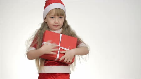 dát : Kid girl in a suit and Santa hat holding a gift in a red box.  Dostupné videozáznamy