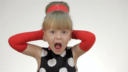 кричать : Kid girl covers his ears with his hands and shouted.