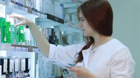 kimyager : Young female pharmacist selecting a medication