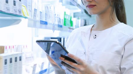 gyógyszertár : Pharmacist working with a tablet-pc Stock mozgókép