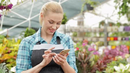 kwiaciarnia : Female florist uses her smartphone at the garden centre