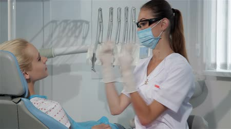 stomatologia : Female dentist begins the checkup of her patient at the dentist cabinet