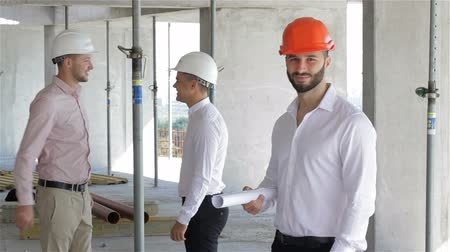 planos : Male builder holds set of plans of building under construction