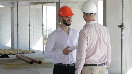 vállalkozó : Architector and builder shake hands at the building under construction
