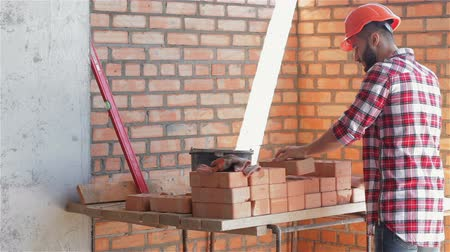 cegła : Builder shifts bricks at the building under construction