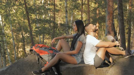 genç çift : Couple of hikers sits back to back on the rock Stok Video