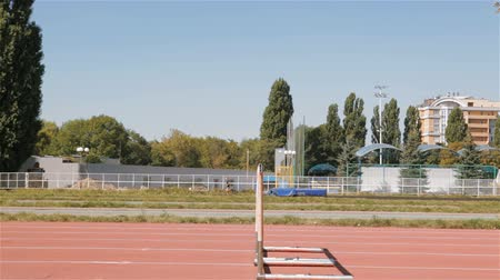 atletismo : Young male athlet jumping over the hurdle at the stadium. Side view of hurdle on the runway. Caucasian sprinter training hurdling
