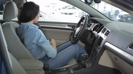 ремень : Young caucasian woman sitting inside the new car at the dealership. Pretty young girl holding her hands on the steering wheel. Attractive brunette woman wearing the seat belt