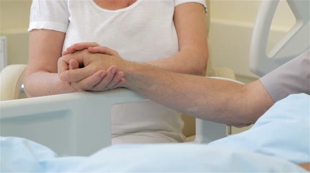 Senior ill man putting his hand on his wifes palm. Close up of female hands holding male hand near the hospital bed. Woman supporting her ill husband at the hospital Стоковые видеозаписи