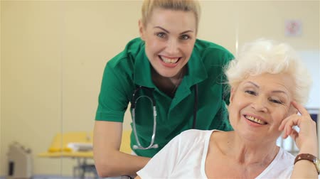 opieka : Attractive young nurse smiling for aged female patient at the hospital. Caucasian blond nurse standing behind senior woman. Pretty nurse in green uniform and old woman smiling for the camera at the hospital