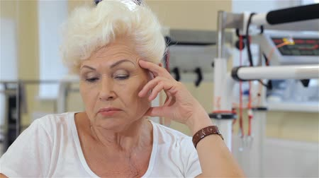 aguardando : Senior woman leaning her head on her hand. Close up of aged caucasian woman at the hospital. Old blond woman sitting on background of rehabilitation equipment Stock Footage