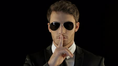 segredo : Stylish man in black suite gesturing silence isolated against black background. Cool caucasian man in aviator sunglasses looking like special agent. Stylish brunette man blowing on his forefinger