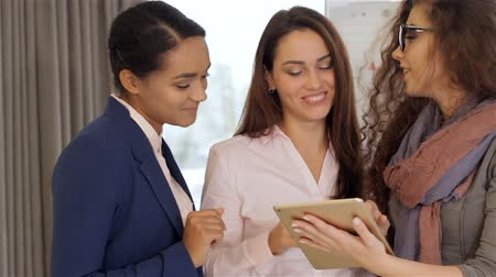 három ember : Three pretty women looking at the tablet at the office. Curly caucasian girl holding tablet in her hands. Black girl and caucasian girl pointing their forefingers on the tablet screen Stock mozgókép