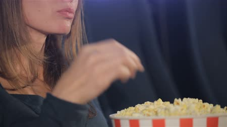 pipoca : Middle aged woman taking flakes of popcorn from the bucket at the movie theater. Close up of caucasian woman slowly eating popcorn. Brownhaired woman holding full bucket of popcorn in her hands