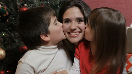 yanak : Caucasian children kissing their mother from both sides. Pretty young woman sitting between little boy and girl. Attractive brunette woman with young kids smiling for the camera Stok Video